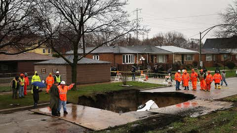 Workers prepare to pull vehicles from a sinkhole that opened up on a residential street in the South Deering neighborhood on April 18, 2013 in Chicago, Ill. (Scott Olson/Getty Images)