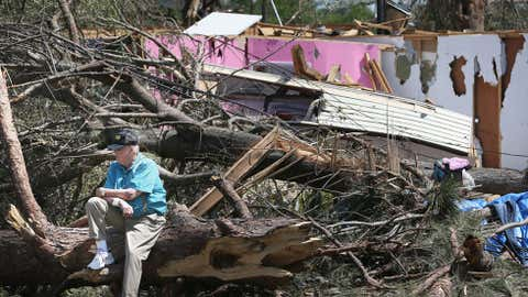 Charles Milam sits on a downed tree in front of what is left of his home where on Monday, April 28, 2014, he was injured by flying debris as he rode out a tornado in Tupelo, Mississippi. (Joe Raedle/Getty Images)