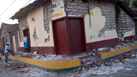 Two men talk outside a home damaged by an earthquake in Nagarote, Nicaragua, Friday, April 11, 2014. (AP Photo/Esteban Felix)
