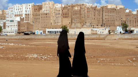 Yemeni women walk past the historical city of Shibam in Hadramaut province of eastern Yemen on October 28, 2008. (KHALED FAZAA/AFP/Getty Images)