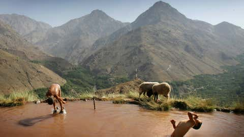 Berber children swim in an irrigation pool on the side of a mountain in the village of Ait Souka on July 25, 2007 in Imlil district, Morocco. The irrigation pool gradually fills up during the day then is drained in the evening to supply crops and the village. (Chris Jackson/Getty Images)