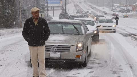 Heavy snow falls in Hartselle, Ala., causing many traffic problems and some fun for children Thursday, Jan. 17, 2013. Motorist James Burton stands in front of his car stranded on US Highway 31 on Hartselle Mountain after the stretch of highway became to slick for many motorists to get up the hill. (AP Photo/The Decatur Daily, Gary Cosby Jr.)