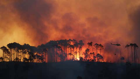 In this photo taken Monday, March 2, 2015, a helicopter dumps water on a fire in the Tokai Forest near Cape Town, South Africa. (AP Photo/Mark Wessels)