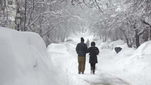 A man and woman stroll down a snow covered street in the Beacon Hill neighborhood of Boston, Saturday, Feb. 9, 2013. The Boston area received about two feet of snow from a winter storm. A howling storm across the Northeast left the New York-to-Boston corridor shrouded in 1 to 3 feet of snow Saturday, stranding motorists on highways overnight and piling up drifts so high that some homeowners couldn't get their doors open. More than 650,000 homes and businesses were left without electricity. (AP Photo/Charles Krupa)