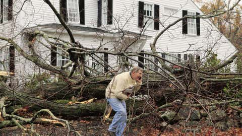John Constantine makes his way out of his house after winds from Hurricane Sandy toppled a tree fell onto it in Andover, Mass. Monday, Oct. 29, 2012.