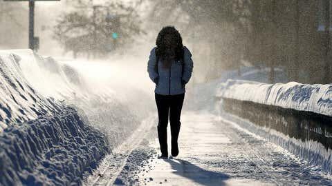 A woman walks through drifting snow in Cambridge, Mass., Sunday, Feb. 15, 2015. (AP Photo/Michael Dwyer)
