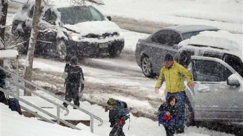 Elementary school students are dropped off at class as Winter Storm Zeus dropped snow over Boulder, Colo., Tuesday April 23, 2013. The Colorado Avalanche Information Center says avalanche danger there is considerable. (AP Photo/Brennan Linsley)