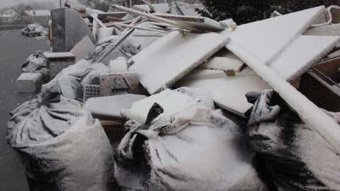 Snow covers debris piles as flood waters start to return to neighborhoods in Point Pleasant Beach, N.J., Wednesday Nov. 7, 2012, as a nor'easter hits. (AP Photo/Wayne Parry)