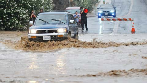 A vehicle drives through a flooded section of the road that was closed off on Pebble Beach Drive in Victorville, California, Sunday, July 19, 2015. (David Pardo/The Victor Valley Daily Press via AP)