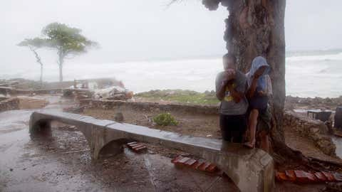 A couple of persons take refuge behind a tree against the strong winds of Tropical Storm Erika, as it approaches Santo Domingo, in the Dominican Republic, Friday, August 28, 2015. Tropical Storm Erika began to lose steam Friday over the Dominican Republic, but it left behind a trail of destruction that included several people killed on the small eastern Caribbean island of Dominica, authorities said. (AP Photo/Tatiana Fernandez)