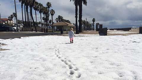 A child leaves footprints in the hail along Huntington Beach, California. (Instagram/Glowy Zoey)