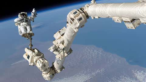 International Space Station's Canadarm2 is used to help astronaut Steve Robinson during the mission's third session of extravehicular activity on Aug. 3, 2005. (NASA)