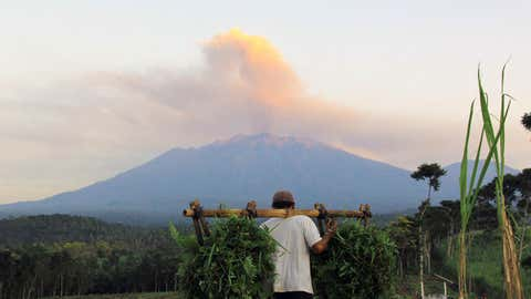 A farmer carries harvested produce while Mount Raung volcano emits steam and ash as seen in the background from Banyuwangi, located in Indonesia's eastern Java island, on July 23, 2015. Mount Raung, which has been rumbling for weeks, sent an ash cloud floating over Bali and eastern Java island disrupting airport operations. Ash spewing from a volcano briefly closed the airport on the Indonesian resort island of Bali on July 22 for the third time this month, forcing the cancellation of flights and stranding tourists during peak holiday season. (STR/AFP/Getty Images)