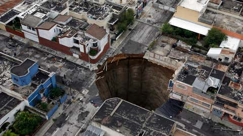 This June 2010 photo shows a sinkhole covering a street intersection in downtown Guatemala City, Guatemala. (AP Photo/Moises Castillo)