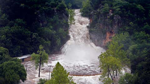 Water pours over Turner Falls and floods the park below on Thursday, June 18, 2015, in Davis, Okla. Tropical Depression Bill swamped Oklahoma and Arkansas on Thursday, pushing rivers toward record levels after the Gulf-fueled storm slowed to a crawl over the nation's midsection. (Steve Sisney/The Oklahoman via AP)