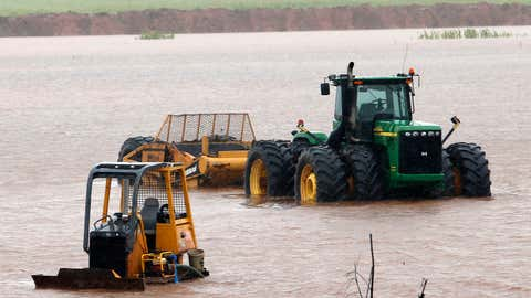 Construction equipment sits in high water from overnight rains off Interstate 35 on Thursday, June 18, 2015, in Pauls Valley, Oklahoma. (Steve Sisney/The Oklahoman via AP)
