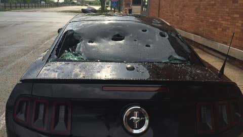 Giant hailstones punched holes in the windows of this Ford Mustang in Tuscola, Illinois, on Wednesday, May 21, 2014. Hail up to 4 inches in diameter fell in the east-central Illinois city. (Photo credit: Twitte/Erin Lacine)