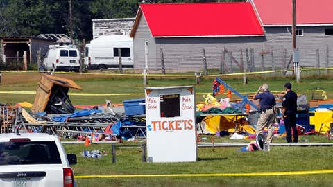 Investigators inspect the site of a circus tent that collapsed during a show by the Walker Brothers International Circus at the Lancaster Fairgrounds in Lancaster, New Hampshire, Tuesday Aug. 4, 2015. A quick moving storm with 60 mph winds hit the tent Monday shortly after the show started, killing a father and daughter. (AP Photo/Jim Cole)