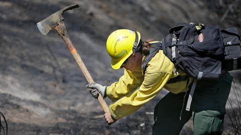 Firefighter Kelly Willman works to put out still smoldering hot spots from a wildfire two days earlier, Tuesday, June 30, 2015, in Wenatchee, Wash. Two dozen homes were destroyed in a fast-moving wildfire Sunday night in Wenatchee,. A handful of businesses also were destroyed when flames spread to the downtown core. (AP Photo/Elaine Thompson)