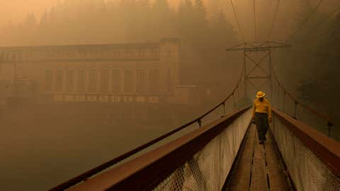 Dennis Godfrey, with the Great Basin Incident Management Team 4, walks across a bridge from the Gorge Powerhouse, Wednesday, Aug. 26, 2015, near Newhalem, Wash. Smoky conditions grounded helicopters and airplanes Wednesday that had been fighting the fires. (Mark Mulligan/The Herald/AP)