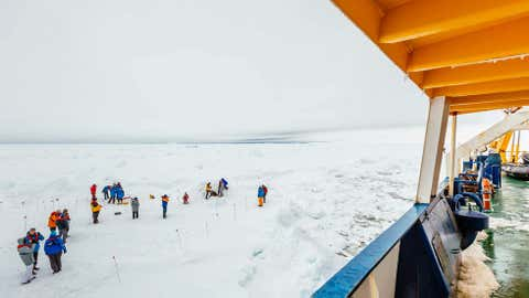 People gather on the ice next the Russian ship MV Akademik Shokalskiy that is trapped in thick Antarctic ice 1,500 nautical miles south of Hobart, Australia. (AP Photo/Australasian Antarctic Expedition/Footloose Fotography, Andrew Peacock)