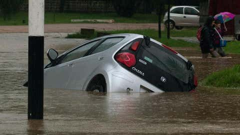 View of a car which fell in a curb in a flooded street in the locality of Solymar, Ciudad de la Costa, Canelones, some 20 km east of Montevideo, during floods caused by heavy rains hitting the country, on February 7, 2014. (MARIANA MENDEZ/AFP/Getty Images)