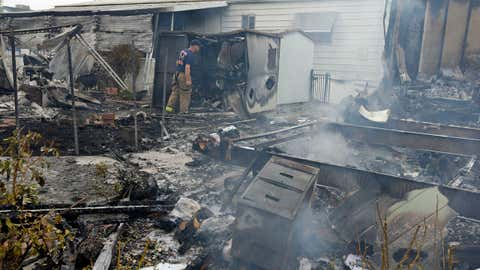 A Napa firefighter inspects one of four mobile homes that were destroyed in a gas fire Sunday, Aug. 24, 2014, at the Napa Valley Mobile Home Park, in Napa, Calif after a preliminary 6.0-magnitude earthquake struck the San Francisco Bay area. (AP Photo/Ben Margot)