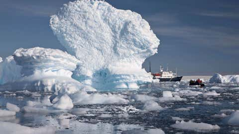 An inflatable boat carries tourists past an iceberg along the Antarctic Peninsula. In a remote, frozen, almost pristine land where the only human residents are involved in research, tourism comes with risks, for both the continent and the tourists. (AP Photo/Aurora Expeditions, Andrew Halsall)