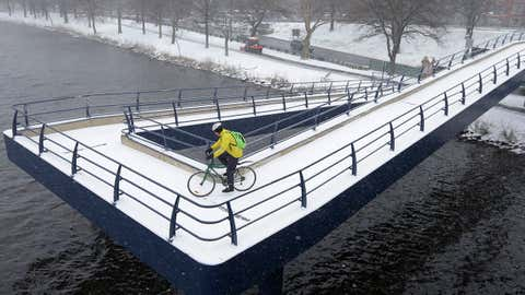 A cyclist rides down a snow-covered ramp over the Charles River, Monday, April 4, 2016, in Boston. An early spring cold front is bringing snow and gusty winds to the Northeast after the region had one of its mildest winters on record. (AP Photo/Steven Senne)