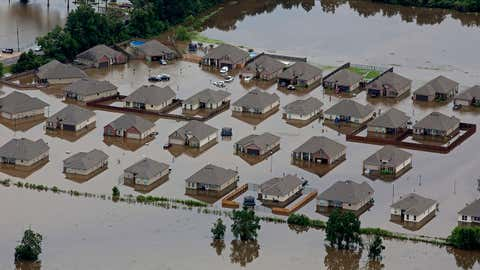 In this aerial photo over Hammond, La., flooded homes are seen off of LA-1064 after heavy rains inundated the region, Saturday, Aug. 13, 2016. (AP Photo/Max Becherer)