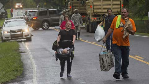 People arrive to be evacuated by members of the Louisiana Army National Guard near Walker, Louisiana, after heavy rains inundating the region, Sunday, Aug. 14, 2016.