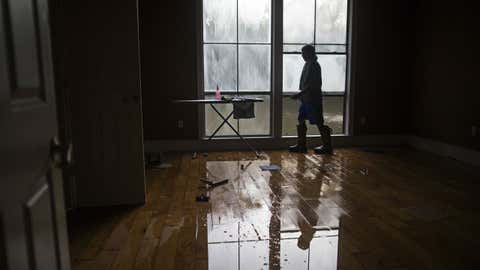 David Key opens the windows in his flooded home in Prairieville, Louisiana, Tuesday, Aug. 16, 2016. Key, an insurance adjuster, fled his home as the flood water was rising with his wife and three children and returned today to assess the damage.