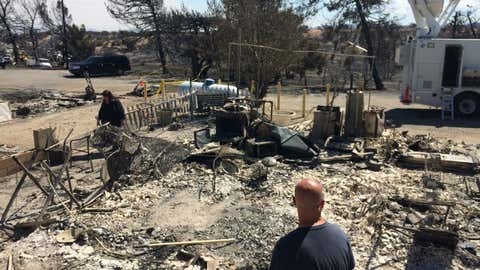 Summit Inn general manager Michelle Keeney, left, and Scott Keeney survey the destruction of their burned home in Oak Hills, Calif., on Friday, Aug. 19, 2016. The Summit Inn, a popular roadside diner at the crest of historic Route 66, was gutted by the Blue Cut wildfire on Tuesday, in the Cajon Pass which was right next door to their home. The Southern California fire unleashed its initial fury on a semi-rural landscape dotted with small ranches and homes in Cajon Pass and on the edge of the Mojave Desert before climbing the mountains.