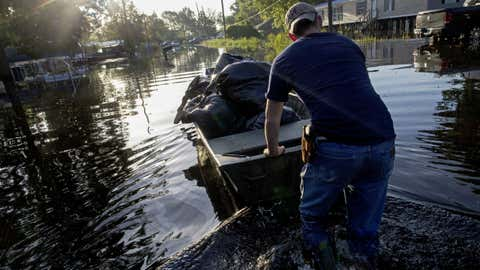Daniel Stover, 17, moves a boat of personal belongings from a friend's home flooded home in Sorrento, La., Saturday, Aug. 20, 2016. Louisiana continues to dig itself out from devastating floods, with search parties going door to door looking for survivors or bodies trapped by flooding.