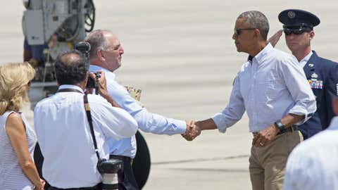 President Barack Obama shakes hands with Louisiana Gov. John Bel Edwards after arriving on Air Force One at the Baton Rouge Metropolitan Airport, Tuesday, Aug. 23, 2016, to survey the flood damaged region in Baton Rouge, Louisiana.