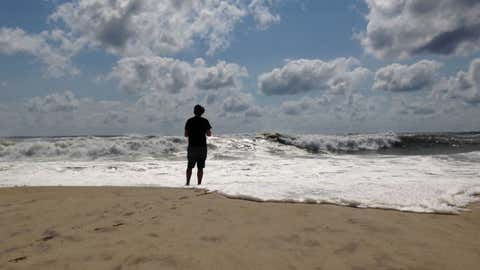 A beachgoer stands at the edge of the water, Sunday, Sept. 4, 2016, in Bridgehampton, New York, on the southeastern shore of Long Island, where the effects of storm system Hermine could be seen in the rough surf and a ban on swimming. Hermine spun away from the U.S. East Coast on Sunday, removing the threat of heavy rain but maintaining enough power to churn dangerous waves and currents and keep beaches off-limits to disappointed swimmers and surfers during the holiday weekend.