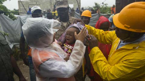 Nice Simon, the city mayor of Tabarre holds a baby as she helps people in the village to evacuate from the Tabarre river area in Haiti. Monday Oct. 3, 2016. The center of Hurricane Matthew is expected to pass near or over southwestern Haiti on Tuesday, but the area is already experiencing rain from the outer bands of the storm. Dieu Nalio Chery/AP Photo)