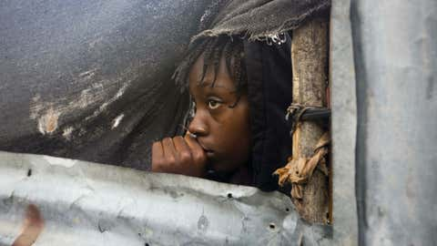 A girl watches as the authorities arrive to evacuate people from her house in Tabarre, Haiti, Monday, Oct. 3, 2016.