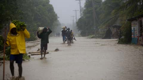 Residents walk in flooded streets as they return to their homes in Leogane, Haiti, Tuesday, Oct. 4, 2016. Matthew slammed into Haiti's southwestern tip with howling, 145 mph winds Tuesday, tearing off roofs in the poor and largely rural area, uprooting trees and leaving rivers bloated and choked with debris.