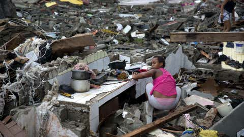 A woman searches amid the rubble of her home destroyed by Hurricane Matthew in Baracoa, Cuba, Wednesday, Oct. 5, 2016.