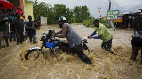 Men push a motorbike through a street flooded by a river that overflowed from heavy rains caused by Hurricane Matthew in Leogane, Haiti, Wednesday, Oct. 5, 2016. Rescue workers in Haiti struggled to reach cutoff towns and learn the full extent of the death and destruction caused by Hurricane Matthew as the storm began battering the Bahamas on Wednesday and triggered large-scale evacuations along the U.S. East Coast.
