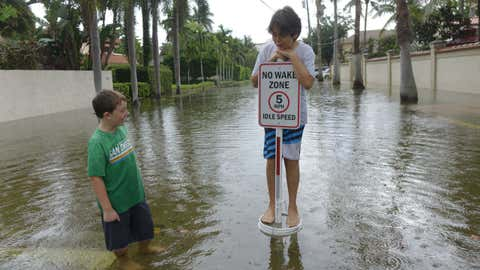 Kalon Neely, left, and Max Obeoholtzer play in flooded streets in the Las Olas Isles area of Fort Lauderdale, Florida, on Hibiscus Place, Sunday, Oct. 16, 2016. King tides, the seasonal higher-than-usual tides capable of swamping coastal communities with sea water, were flooding parts of coastal Fort Lauderdale on Sunday morning.