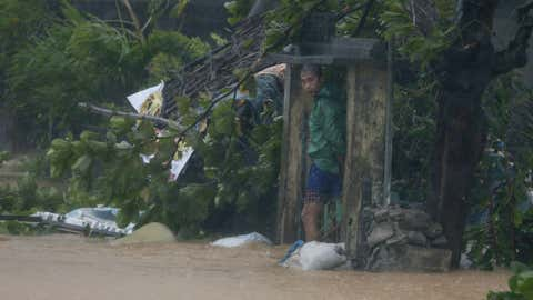 A man takes shelter by the concrete gates of his flooded house at the height of Super Typhoon Haima which lashes Narvacan township, Ilocos Sur province, Philippines Thursday Oct. 20, 2016.