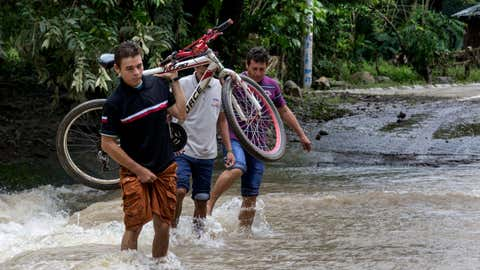 A young man carries his bicycle across a road that flooded after the passing of Hurricane Otto in Cardenas, Nicaragua, on Nov. 25, 2016.