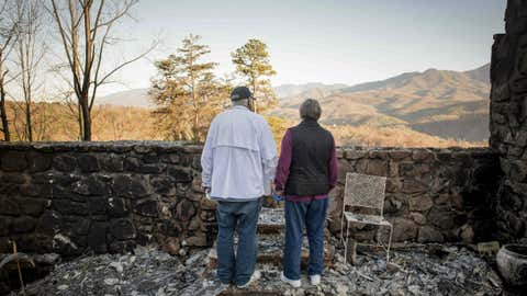 Richard T. Ramsey and Sue Ramsey hold hands while looking at the skyline from the remains of their house of 41 years, Thursday, Dec. 1, 2016, in Gatlinburg, Tennessee. They safely evacuated from their home as wildfire approached Monday evening. (Andrew Nelles/The Tennessean via AP)