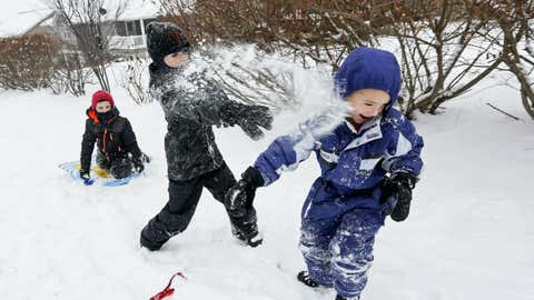 Brandon Grimes, from left, 9, Braeden Beasley, 8, and Austin Ricks, 4, have a snowball fight in Asbury, Iowa, on Sunday, Dec. 11, 2016. The Dubuque, Iowa, area received 4 inches of snow overnight, less than forecasters had expected. (Nicki Kohl/Telegraph Herald via AP)