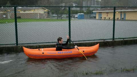 Julian LePelch paddles his kayak past a flooded field at Tamalpais High School Thursday, Dec. 15, 2016, in Mill Valley, California. (AP Photo/Eric Risberg)