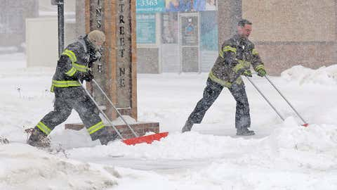 Mandan firefighters Shane Weltikol, left, and Chad Nicklos clear accumulating snow from outside the firehouse in downtown Mandan, N.D., as Winter Storm Europa intensifies on Sunday, Dec. 25, 2016. Most of the Dakotas and southwest Minnesota had turned into a slippery mess due to freezing rain Sunday morning before snow arrived later in the day as temperatures fell. (Tom Stromme/The Bismarck Tribune via AP)