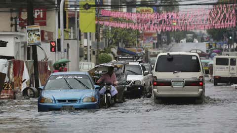 Vehicles navigate a flood-prone area caused by rains from Typhoon Nock-Ten in Quezon city, north of Manila, Philippines on Monday, Dec. 26, 2016. The powerful typhoon slammed into the eastern Philippines on Christmas Day, spoiling the biggest holiday in Asia's largest Catholic nation, where a governor offered roast pig to entice villagers to abandon family celebrations for emergency shelters. (AP Photo/Aaron Favila)