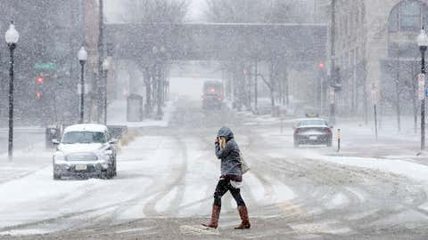 A woman crosses 16th street during a snow storm Friday, Feb 24, 2017, in Omaha, Neb. (Brendan Sullivan/Omaha World-Herald via AP)